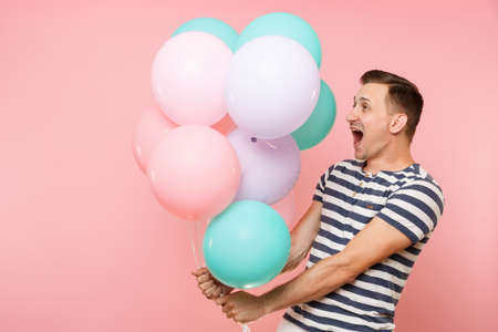 Portrait of fascinating young happy man wearing striped t-shirt holding colorful air balloons isolated on bright trending pink background. People sincere emotions lifestyle concept. Advertising area