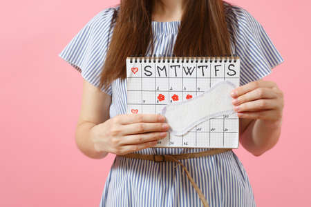 Portrait woman in blue dress, hat holding sanitary napkin, female periods calendar for checking menstruation days isolated on pink background. Medical, healthcare, gynecological concept. Copy space Stock Photo