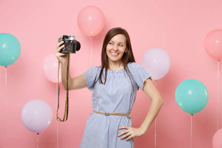 Portrait of attractive smiling happy woman in blue dress do selfie on retro vintage photo camera on pastel pink background with colorful air balloons. Birthday holiday party, people sincere emotions