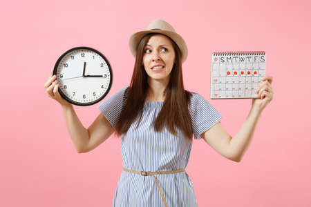 Shocked confused sad woman in blue dress holding round clock, periods calendar for checking menstruation days isolated on trending pink background. Medical gynecological concept. Copy space Stock Photo
