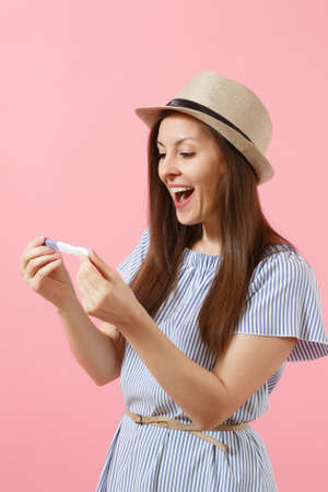 Excited happy woman in blue dress, hat hold in hand, looking at pregnancy test isolated on pink background. Medical healthcare gynecological, pregnancy fertility maternity people concept. Copy space