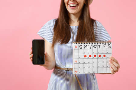 Woman holding female periods calendar for checking menstruation days, mobile phone with blank black empty screen isolated on pink background. Medical, healthcare, gynecological concept. Copy space