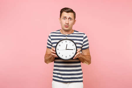 Portrait of shocked sad upset man wearing striped t-shirt holding round clock, copy space isolated on trending pastel pink background. People sincere emotions lifestyle concept. Time is running out
