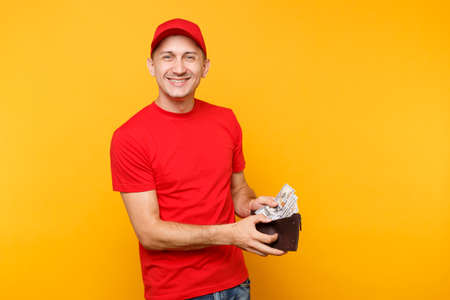 Delivery man in red uniform isolated on yellow orange background. Professional male employee in cap, t-shirt courier or dealer holding bundle lots of dollars, cash money. Service concept. Copy space Stok Fotoğraf