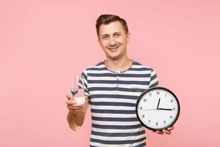 Portrait of happy caucasian man in striped t-shirt holding round clock, clear fresh pure water in glass isolated on trending pastel pink background. People healthy lifestyle concept. Time running out Banque d'images - 106021998