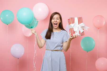 Portrait of overjoyed happy woman wearing blue dress holding red box with gift present and colorful air balloons on bright pink background. Birthday holiday party, people sincere emotions concept