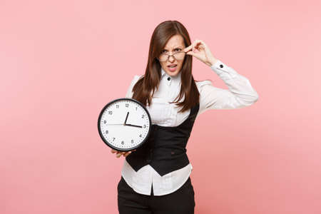 Young irritated dissatisfied business woman in black suit, glasses holding alarm clock isolated on pastel pink background. Lady boss. Achievement career wealth concept. Copy space for advertisement