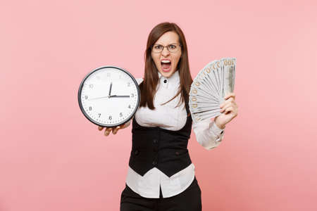 Young irritated business woman in glasses scream hold bundle lots of dollars cash money and alarm clock isolated on pink background. Lady boss. Achievement career wealth. Copy space for advertisement