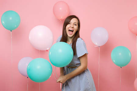 Portrait of surprised joyful woman with opened mouth wearing blue dress holding colorful air balloons on bright trending pink background. Birthday holiday party, people sincere emotions concept