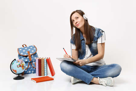 Young pretty woman student in headphones looking up dreaming listen music writing notes on notebook near globe backpack books isolated on white background. Education in high school university college Archivio Fotografico