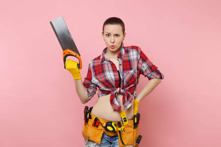 Strong young handyman woman in plaid shirt, denim shorts, kit tools belt full of different instruments holding saw isolated on pink background. Female in male work. Renovation and occupation concept