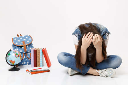 Portrait of young upset depressive woman student leaning clinging to head, sitting looking on globe, backpack, school books isolated on white background. Education in high school university college Stock Photo