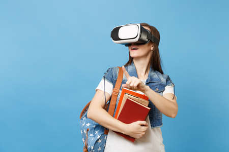 Young woman student in virtual reality glassess hold books touch something like push on button, pointing at floating virtual screen isolated on blue background. Education in school university college