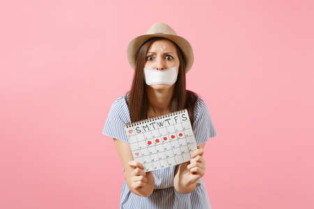 Portrait of woman holding female periods calendar for checking menstruation days, closed mouth with sanitary napkin isolated on pink background. Medical, healthcare, gynecological concept. Copy space