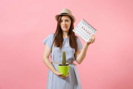 Sad illness woman in blue dress holding green cactus, periods calendar for checking menstruation days isolated on pink background. Medical, healthcare, gynecological, abdomen pain concept. Copy space Banco de Imagens