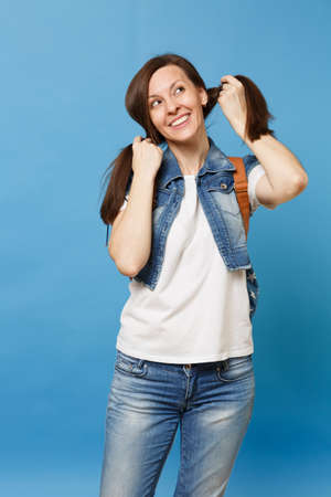Portrait of young curious cute woman student in denim clothes with backpack dreaming looking up and holding ponytails isolated on blue background. Education in college. Copy space for advertisement Banque d'images