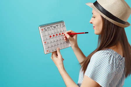 Back rear view of woman in blue dress, hat holding red pencil, female periods calendar for checking menstruation days isolated on blue background. Medical healthcare, gynecological concept. Stock Photo