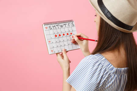 Back rear view woman in blue dress, hat holding red pencil, female periods calendar for checking menstruation days isolated on pink background. Medical healthcare, gynecological concept. Copy space