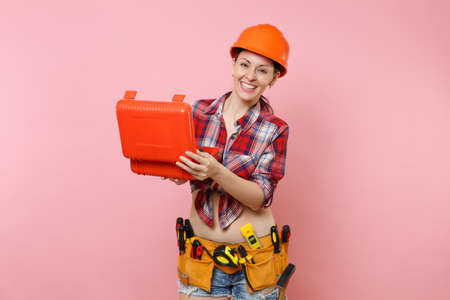 Strong young handyman woman in orange helmet, plaid shirt, denim shorts, kit tools belt full of instruments, toolbox isolated on pink background. Female in male work. Renovation occupation concept