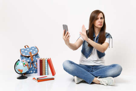 Young concerned dissatisfied woman student hold mobile phone show stop gesture with palm sit near globe backpack school books isolated on white background. Education in high school university college