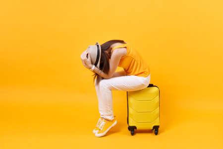 Verärgerte Touristenfrau im Sommer lässige Kleidung sitzen auf Koffer setzen Hände auf Kopf lokalisiert auf gelbem orange Hintergrund. Frau, die ins Ausland reist, um am Wochenendausflug zu reisen. Flugkonzept