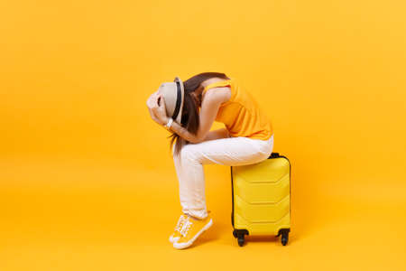 Upset tourist woman in summer casual clothes sit on suitcase put hands on head isolated on yellow orange background. Female traveling abroad to travel on weekends getaway. Air flight journey concept
