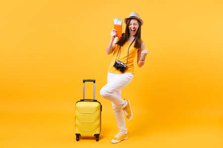 Excited happy tourist woman in summer hat with passport, ticket, suitcase, doing winner gesture isolated on yellow background. Female traveling abroad to travel weekends getaway. Air flight concept