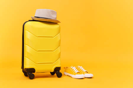 Traveler tourist suitcase trunk luggage bag with summer hat sneakers isolated on yellow orange background. Passenger things accessories for traveling abroad to travel concept. Copy space workspace