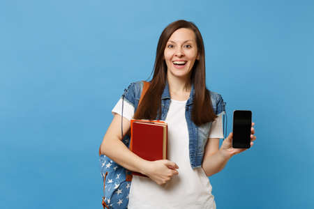 Young excited pretty woman student in denim clothes with backpack hold school books mobile phone with blank black empty screen isolated on blue background. Education in high school university college Stock Photo