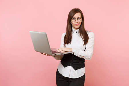 Young puzzled concerned business woman in suit and glasses working in laptop pc computer isolated on pastel pink background. Lady boss. Achievement career wealth concept. Copy space for advertisement Stock Photo