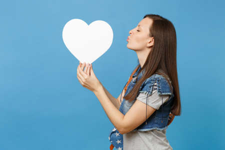 Portrait of young tender beautiful woman student with backpack sending air kiss to white heart with copy space in hand isolated on blue background. Education in college. Copy space for advertisement