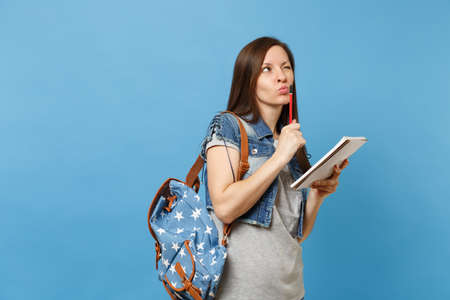 Portrait of young pensive woman student in denim clothes with backpack taking exam thinking about test holding notebook pencil isolated on blue background. Education in high school university college Foto de archivo