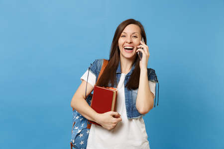 Young laughing woman student with backpack hold school books talking on mobile phone conducting pleasant conversation isolated on blue background. Education in high school university college concept