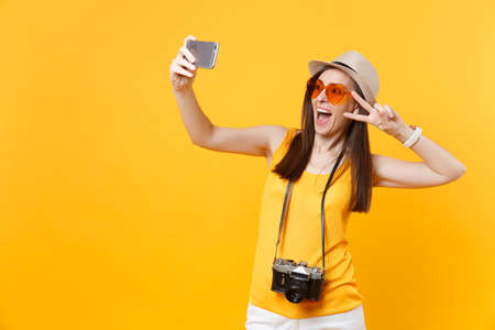 Tourist woman in summer casual clothes, hat doing taking selfie shot on mobile phone isolated on yellow background. Female passenger traveling abroad to travel on weekends getaway. Air flight concept Banque d'images