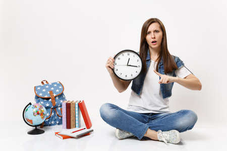 Young puzzled woman student in denim clothes pointing index finger on alarm clock sitting near globe, backpack, school books isolated on white background. Education in high school university college