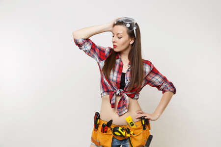 Strong young handyman woman in plaid top shirt, denim shorts, kit tools belt full of instruments in protective goggles isolated on white background. Female in male work. Copy space for advertisement