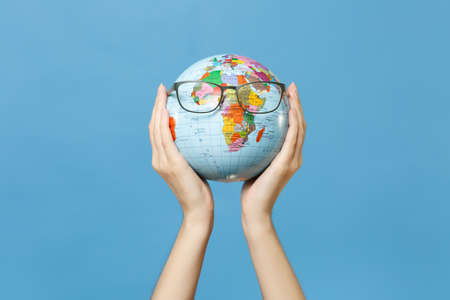 Close up female hold in hands geographic political world globe with glasses isolated on blue background. Learning about countries. Education in high school university concept. Travel journey abroad
