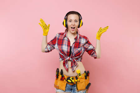 Handyman woman in plaid shirt, denim shorts, yellow gloves, noise insulated headphones, kit tools belt full of variety instruments isolated on pink background. Female in male work. Renovation concept