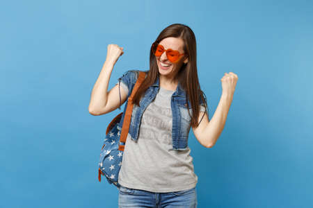 Young woman student with closed eyes with backpack in orange heart glasses clenching fists like winner or happy human isolated on blue background. Education in college. Copy space for advertisement