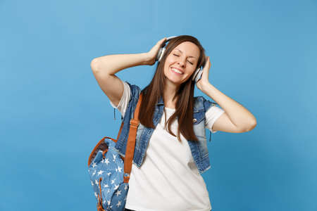 Young relaxed woman student with closed eyes in denim clothes with backpack keeping hand on headphones listen music isolated on blue background. Education in high school. Copy space for advertisement Stock Photo