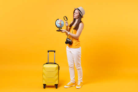 Traveler tourist woman in summer casual clothes, hat with globe, suitcase isolated on yellow orange background. Passenger traveling abroad to travel on weekends getaway. Air flight journey concept