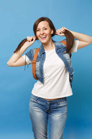 Portrait of young funny pretty smiling woman student in white t-shirt, denim clothes with backpack holding ponytails isolated on blue background. Education in college. Copy space for advertisement
