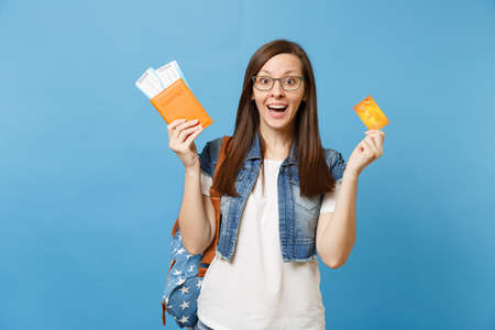 Young shocked excited woman student with backpack spread hands holding passport boarding pass ticket credit card isolated on blue background. Education in university college abroad. Air travel flight Stock Photo