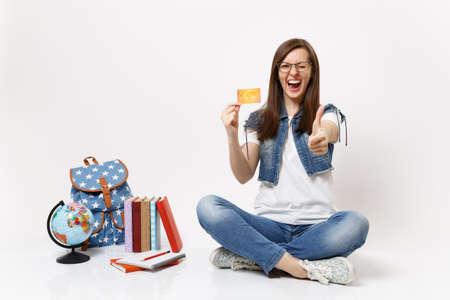Joven estudiante feliz feliz con gafas parpadeando sosteniendo la tarjeta de crédito mostrando el pulgar hacia arriba cerca de los libros de la mochila del globo aislados sobre fondo blanco. Educación en la escuela secundaria universitaria