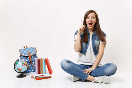 Young excited woman student enlightened with new thought, idea pointing index finger up sit near globe, backpack school books isolated on white background. Education in high school university college