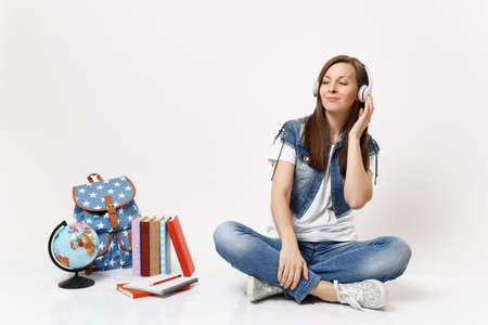 Young relaxed tender woman student with closed eyes in headphones listening music sitting near globe, backpack, school books isolated on white background. Education in high school university college
