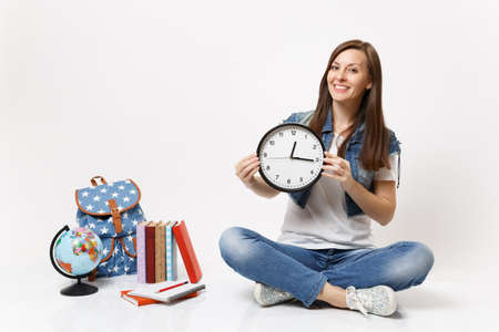 Young smiling pleasant woman student in denim clothes holding alarm clock sitting near globe, backpack, school books isolated on white background. Education in high school university college concept 版權商用圖片