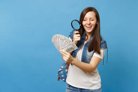 Young curious woman student with backpack look on bundle lots of dollars, cash money with magnifying glass check banknotes isolated on blue background. Verification for authenticity of money concept