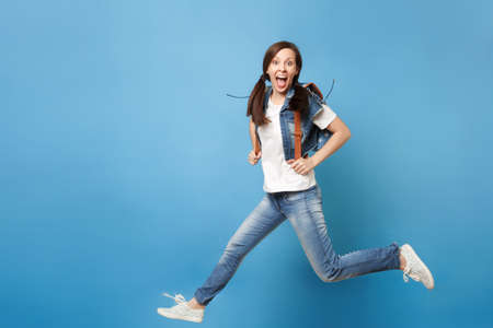Full length portrait of young excited cheerful woman student with opened mouth with backpack jumping spreading legs isolated on blue background. Education in university. Copy space for advertisement