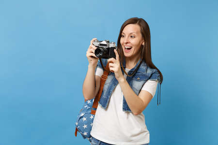 Portrait of young excited woman student with opened mouth with backpack take pictures on retro vintage photo camera isolated on blue background. Education in university. Copy space for advertisement